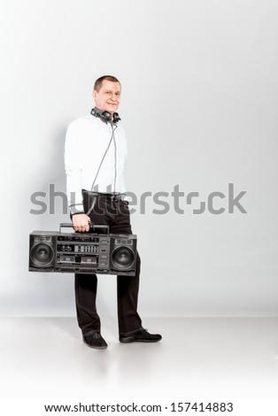Handsome man posing in studio with audio recorder - stock photo