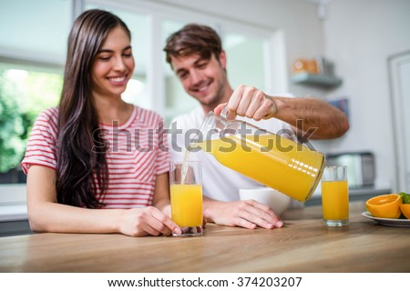 Handsome man pouring orange juice in a glass in kitchen - stock photo