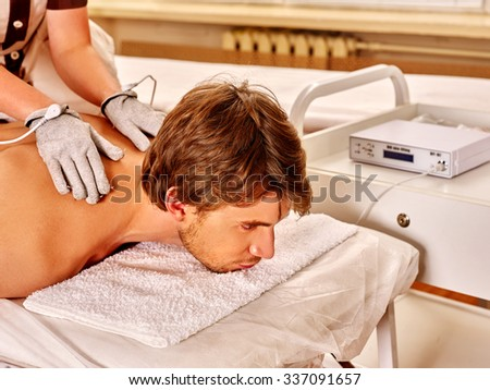 Handsome man  receiving electric body back massage at beauty salon. Beautician wearing electricity gloves.  - stock photo