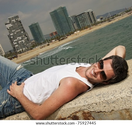 Handsome man relaxing near the sea - stock photo