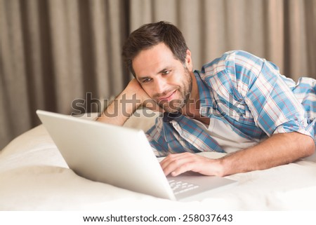 Handsome man relaxing on his bed with laptop at home in bedroom - stock photo