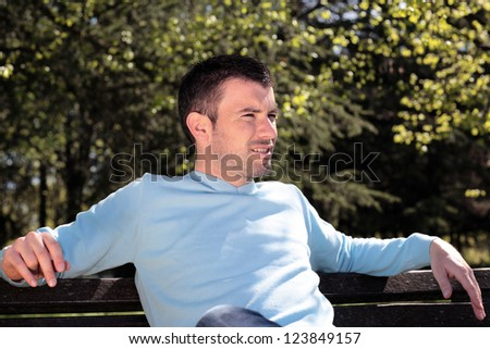 handsome man resting on a bench in a park - stock photo