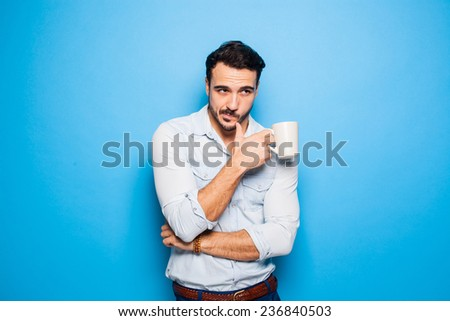 handsome man scratching his beard, holding a cup of coffee in hand - stock photo