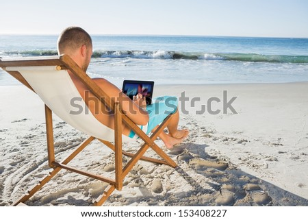 Handsome man scrolling on his tablet pc on the beach - stock photo