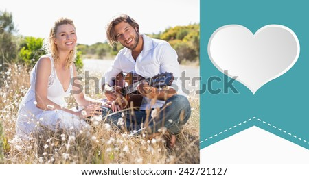 Handsome man serenading his girlfriend with guitar against heart label - stock photo