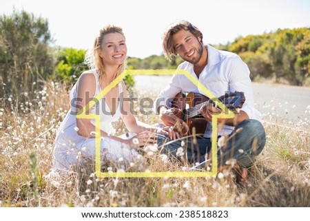 Handsome man serenading his girlfriend with guitar against house outline - stock photo