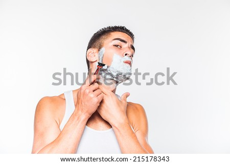 handsome man shaving his beard with a razor, on white background - stock photo