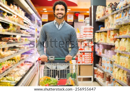 Handsome man shopping in a supermarket - stock photo