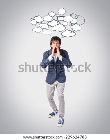 Handsome man shouting over grey background - stock photo