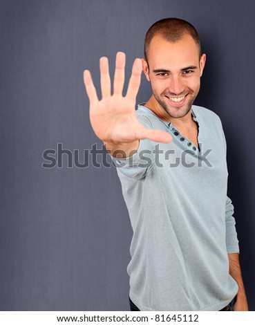 Handsome man showing hand to camera - stock photo