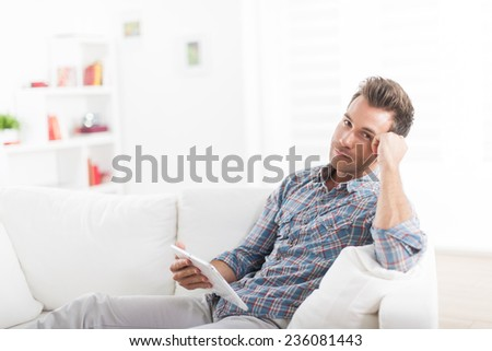 handsome man sitting barefoot on a white sofa and using a digital tablet - stock photo