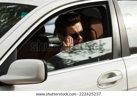 Handsome man sitting in car - stock photo