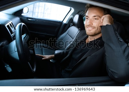 Handsome man sitting in limousine, talking on cellphone, smiling. - stock photo