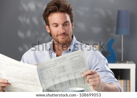 Handsome man sitting in living room, reading newspaper, smiling. - stock photo