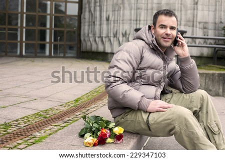 handsome man sitting outside on stairs with a bunch of roses and talking on the phone - stock photo