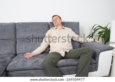 Handsome man sleeping on his couch at his home - stock photo