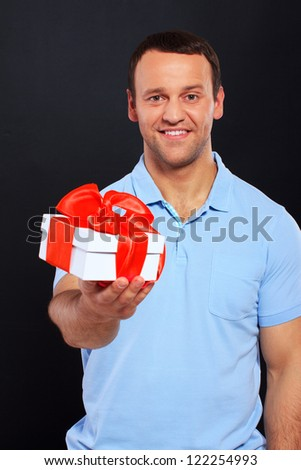 Handsome man smiling and holding a gift over a black background - stock photo