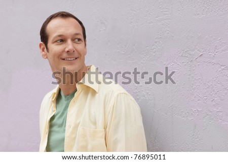 Handsome man smiling and looking over shoulder - stock photo
