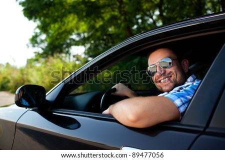 Handsome man smiling in his own car - stock photo