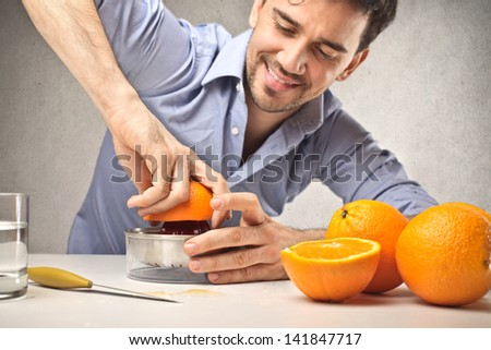 handsome man squeezes oranges - stock photo