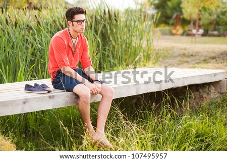 handsome man standing on a bridge by the lake - stock photo