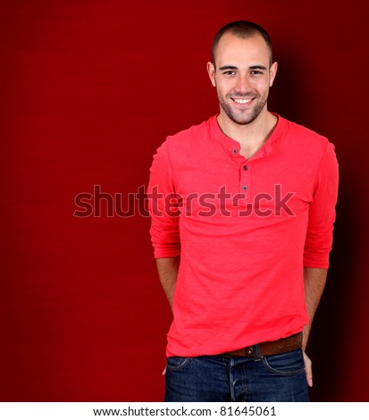 Handsome man standing on red background - stock photo