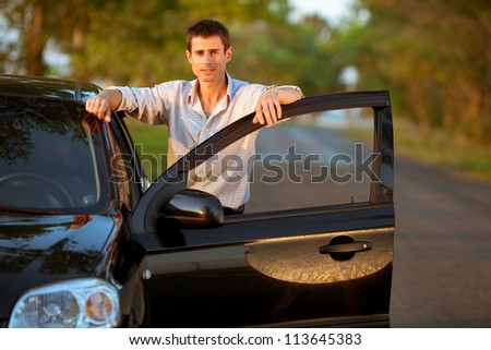 Handsome man standing on the road near opened door of his car. - stock photo