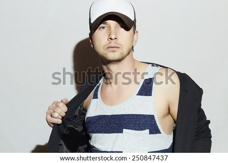 Handsome Man. Stylish Boy in cap. Casual Fashion.posing Young man model - stock photo