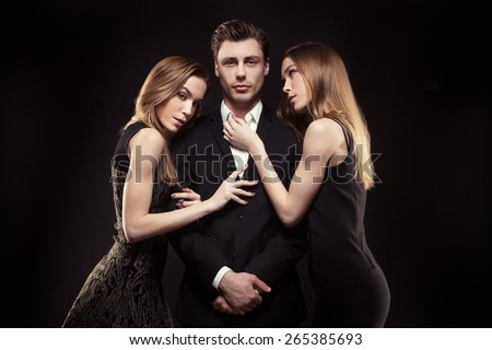 handsome man surrounded by beautiful girls in the studio. concept of success, 2 girls, twins - stock photo