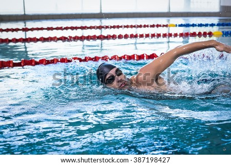 Handsome man swimming in the pool - stock photo