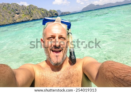 Handsome man taking a selfie during islands hopping at El Nido in Palawan - Boat trip snorkeling in exotic scenarios - Adventure travel lifestyle around Philippines - Composition with tilted horizon  - stock photo