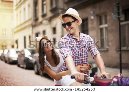 Handsome man taking his girlfriend on bicycle rack - stock photo