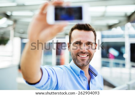 Handsome man taking selfie outside the office - stock photo