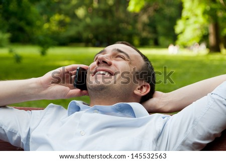 Handsome man talking on phone while sitting on bench in park - stock photo