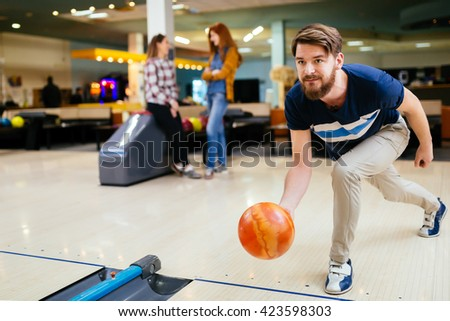 Handsome man throwing bowling ball - stock photo