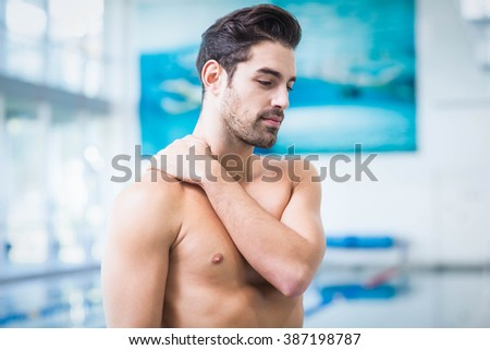 Handsome man touching his shoulder at the pool - stock photo