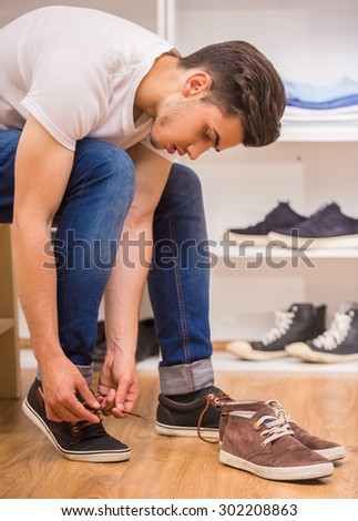Handsome man tying shoe laces while sitting on chair at the dressing room. - stock photo