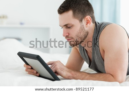 Handsome man using a tablet computer while lying on his belly in his bedroom - stock photo