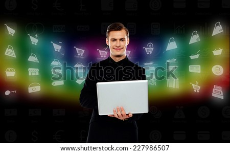 Handsome man using his laptop, different icons background - stock photo