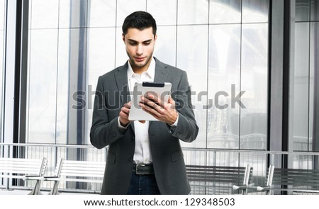 Handsome man using his tablet computer - stock photo