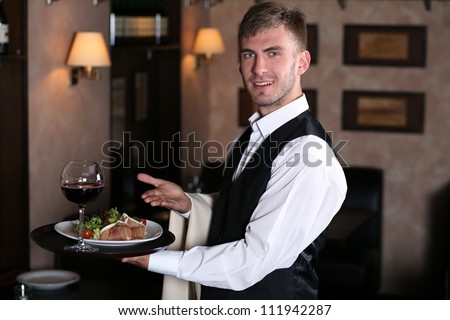 handsome man waiter in uniform at restaurant - stock photo