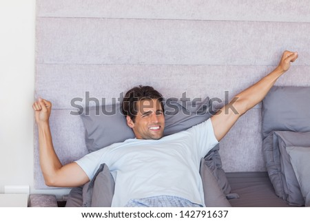 Handsome man waking up and stretching in his bed - stock photo