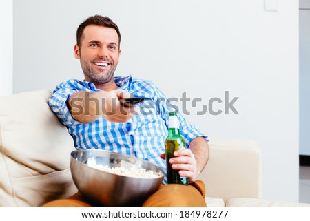 Handsome man watching TV with a beer and popcorn - stock photo