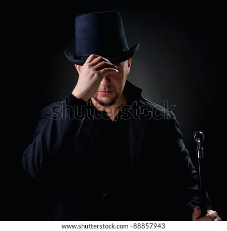 Handsome man wearing black hat and jacket holding stick over black background - stock photo