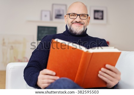 Handsome man wearing glasses relaxing at home reading a book on a sofa in the living room looking at the camera with a warm friendly smile - stock photo