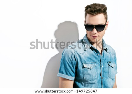 handsome man wearing jeans and sunglasses.studio - stock photo