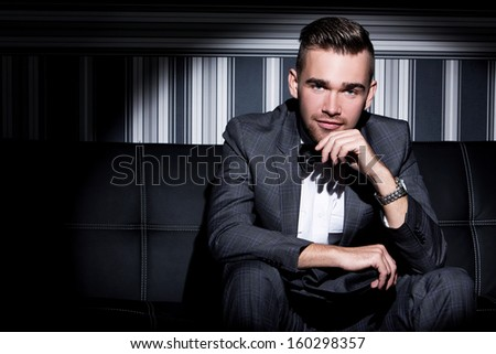 Handsome man with a beard who is wearing a dark suit and a tie is posing over a striped background - stock photo