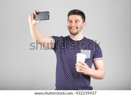 Handsome man with a coffee to go taking selfie on own phone for social networks. Isolated on gray - stock photo