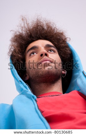 handsome man with a hood, view from below. Studio shot - stock photo
