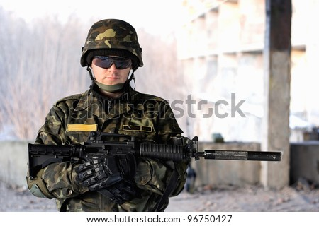 Handsome man with a rifle in front of neglected house - stock photo